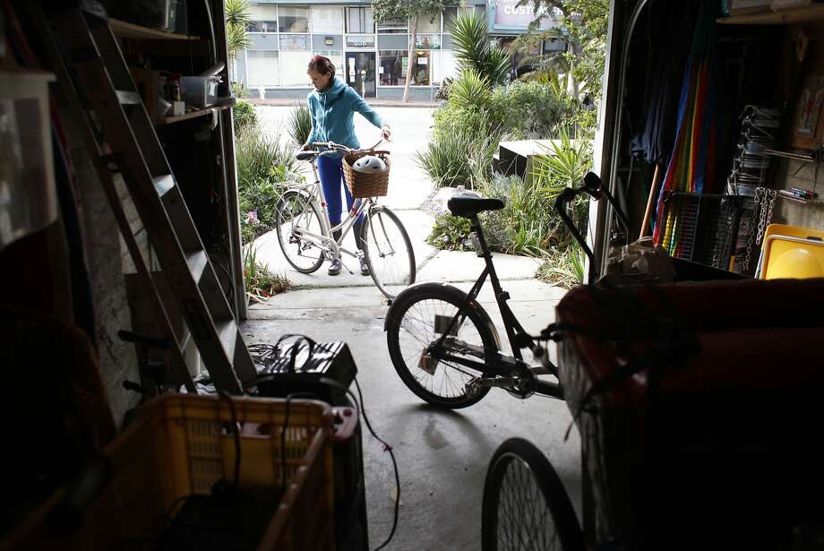 Kimberly Conley puts a bicycle into her garage where she and her husband keep their bicycles and other items rather than cars, Monday January 6, 2014, in San Francisco, Calif. They have turned their driveway into a parklet for public uses. Photo: Lacy Atkins, The Chronicle