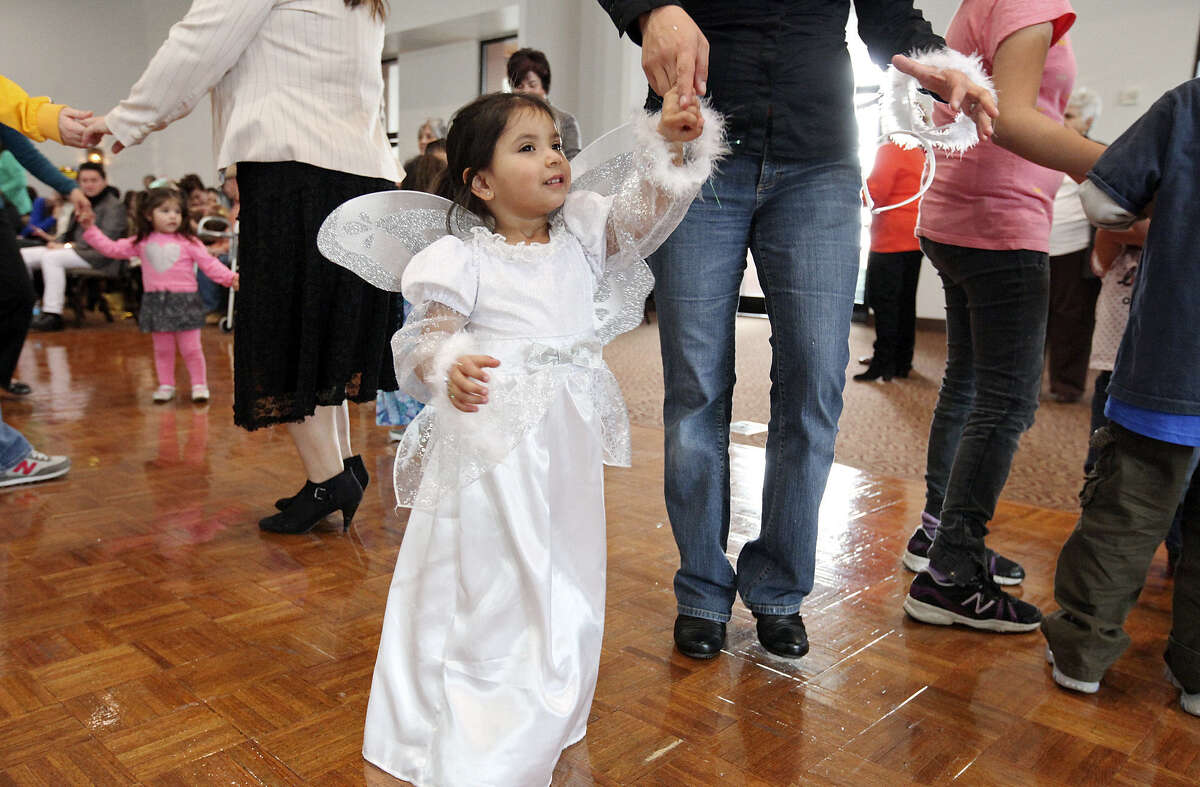 Wearing an angel costume, Viviana Ramos, 2, dances with her mom, Deborah Ramos, during the Puerto Rican Heritage Society's Three Kings Day celebration held Sunday at the AT&T Community Centre, a San Fernando Cathedral venue. About 300 people attended.