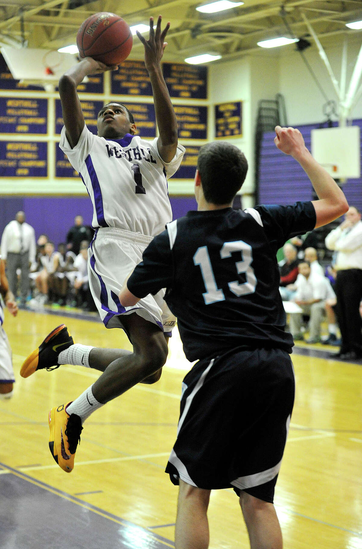 Westhill's Jeremiah Livingston leaps to shoot over Wilton's Matthew Shifrin during their basketball game at Westhill High School in Stamford, Conn., on Monday, Jan. 6, 2014. Westhill won, 51-43.
