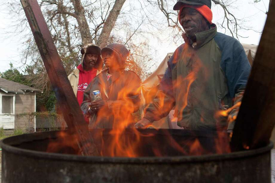At left, Terrance Franklin, Gladys Hemphill and Henry Smith stay warm outside near the corner of Drew Street and Cullen Boulevard with a barrel fire Monday, Jan. 6, 2014, in Houston. 