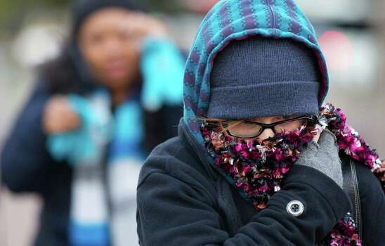 "Kristina Nichols keeps bundled while she waked to work downtown as temperatures dropped Monday, Jan. 6, 2014, in Houston. ""I wish we had more of a winter,"" she said. ""The only thing missing is snow."" Photo: Johnny Hanson, Houston Chronicle / © 2014  Houston Chronicle"
