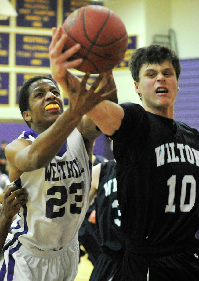 Westhill's Juan De La Cruz and Wilton's Lucas Savoie compete for the loose ball during their basketball game at Westhill High School in Stamford, Conn., on Monday, Jan. 6, 2014. Westhill won, 51-43. Photo: Jason Rearick / Stamford Advocate