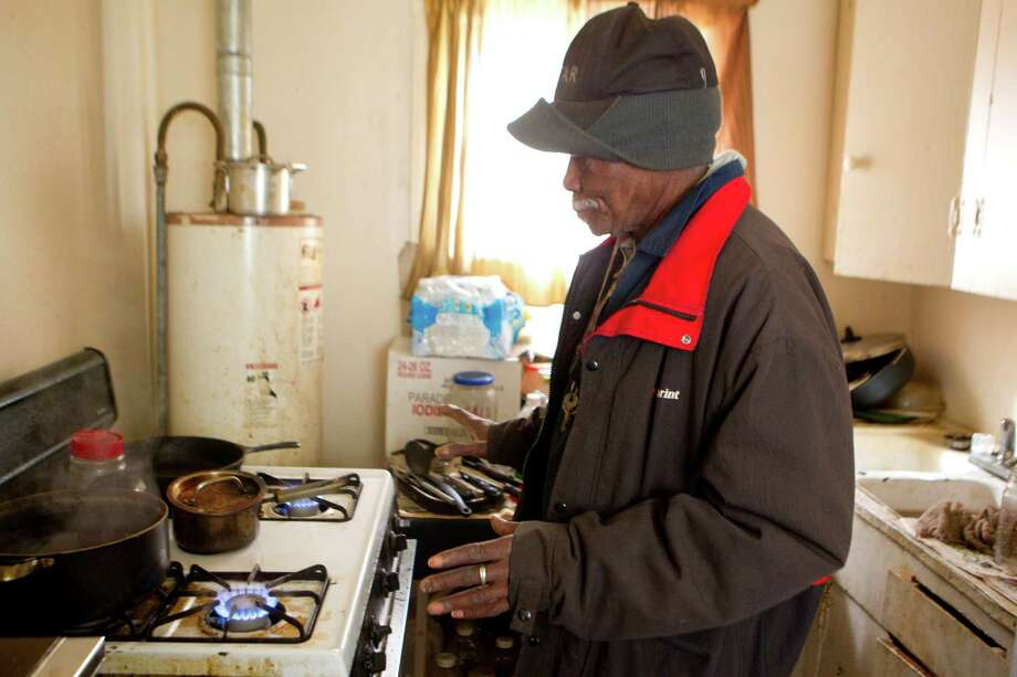 "Joe Bryant, 75, stands in his kitchen with all of the burners on his gas stove on to heat his Third Ward home Monday, Jan. 6, 2014, in Houston. ""I'm a survivor,"" said Bryant, who has been living with out heat for the past three years. ""You only need it but a couple days out of the year."" 