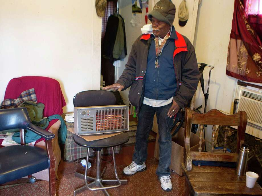 """Joe Bryant, 75, stands next to the electric space heater he uses to heat his Third Ward home Monday, Jan. 6, 2014, in Houston. """"I'm a survivor,"""" said Bryant, who has been living with out heat for the past three years. """"You only need it but a couple days out of the year.""""  Bryant also turns on his gas stove to help heat his home and says he doesn't worry about a fire. """"I turn them off at night and I use two comforters on my bed."""" Photo: Johnny Hanson, Houston Chronicle / © 2014  Houston Chronicle"""