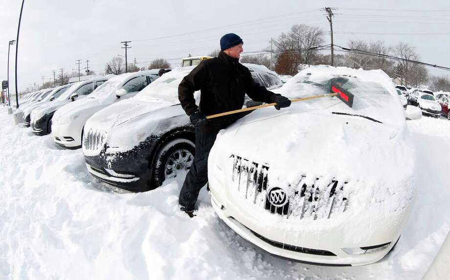 Matt Frame brushes off a Buick at Ray Laethem Buick-GMC in Detroit, Monday, Jan. 6, 2014. Michigan residents are preparing for diving temperatures as they dig out from more than 15 inches of snow in places. Snow wrapped up after starting during the weekend. Roads are slippery, with numerous crashes. In the southern Lower Peninsula, temperatures are to drop late Monday or early Tuesday as low as minus 15. Photo: Paul Sancya, Associated Press / AP