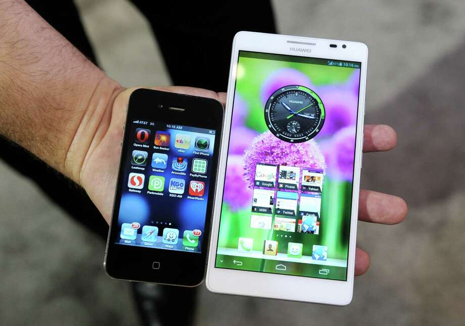 "The Huawei Ascend Mate ""phablet"" (right), a combination phone-tablet, is displayed next to an Apple iPhone at the 2013 International Computer Electronics Show in Las Vegas. Photo: David Becker / Getty Images / 2013 Getty Images"