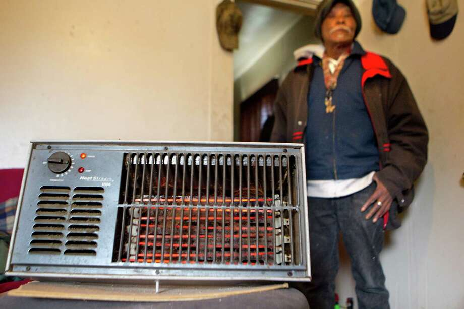 """""""I'm a survivor,"""" says Joe Bryant, 75, who has been living without heat for the past three years. """"You only need it but a couple days out of the year."""" Bryant uses his electric space heater to heat his Third Ward home Monday.  Photo: Johnny Hanson, Staff / © 2014  Houston Chronicle"""