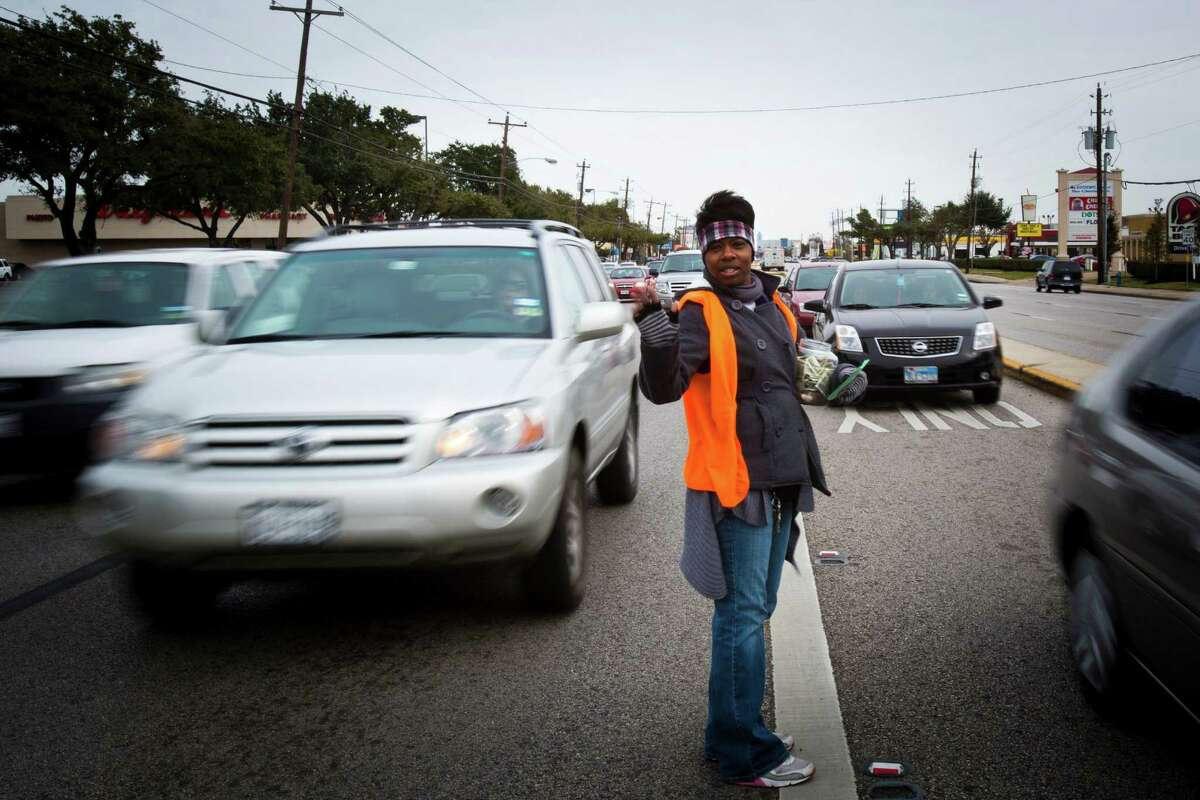 Racquel Miller, a rehabilitated former cocaine user, waves to cars Monday as they pass by after asking for donations to sustain Restoration Houston Ministry, which has helped her stay away from drugs.