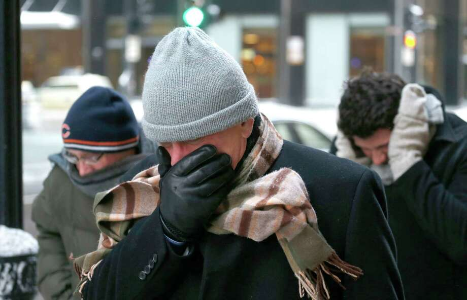 "Three men protect themselves from the elements as they walk in Chicago's Loop with temperatures well below zero and wind chills expected to reach 40 to 50 below Monday, Jan. 6, 2014, in Chicago. A whirlpool of frigid, dense air known as a ""polar vortex"" descended Monday into much of the U.S. (AP Photo/Charles Rex Arbogast) ORG XMIT: ILCA112 Photo: Charles Rex Arbogast / AP"