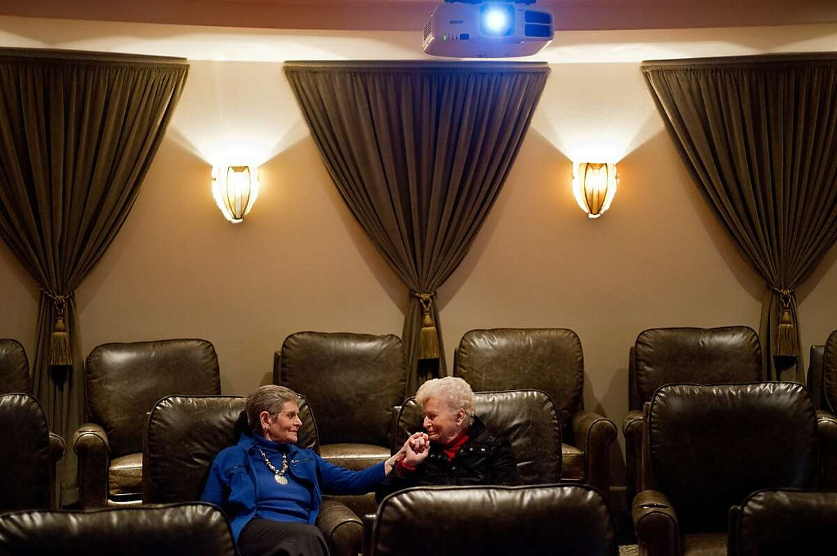 Matile Rothschild, left, and Joan Zimmerman hold hands as they sit in the movie theater of the Fountaingrove Lodge, the country's first LGBT retirement community with the option of continuing care services, where they reside in Santa Rosa, Calif., on December 30, 2013.