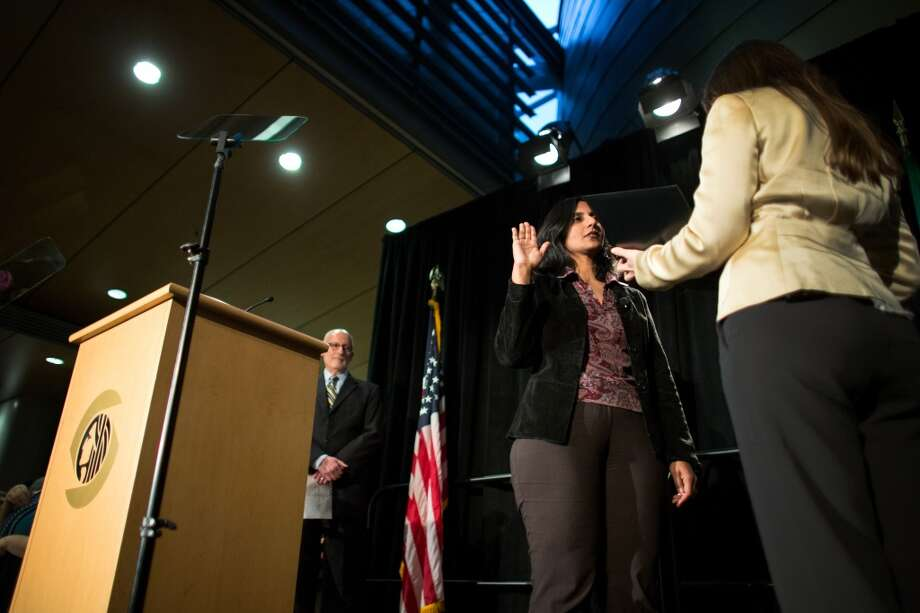 Seattle City Councilmember Kshama Sawant is sworn-in on Monday, January 6, 2014 at Seattle City Hall. Hundreds of people packed the lobby of City Hall for the swearing-in of city council members, the city attorney and the new mayor. Photo: JOSHUA TRUJILLO, SEATTLEPI.COM