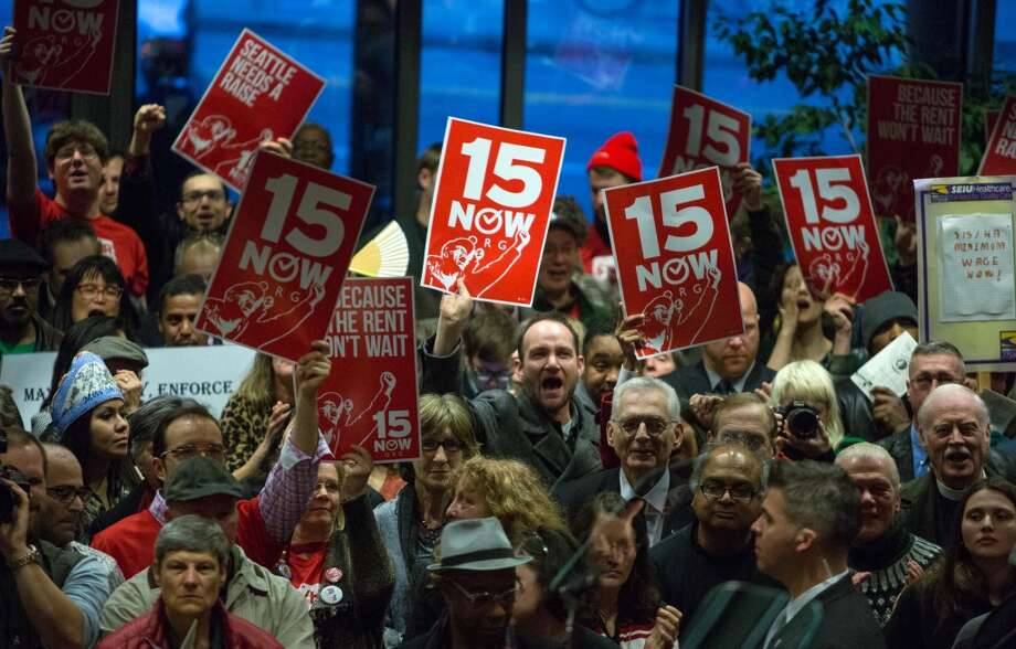 Supporters of a $15 per hour minimum wage chant during a swearing in ceremony on Monday, January 6, 2014 at Seattle City Hall. Kshama Sawant, the new socialist councilmember, is a champion of raising the minimum wage. Photo: JOSHUA TRUJILLO, SEATTLEPI.COM