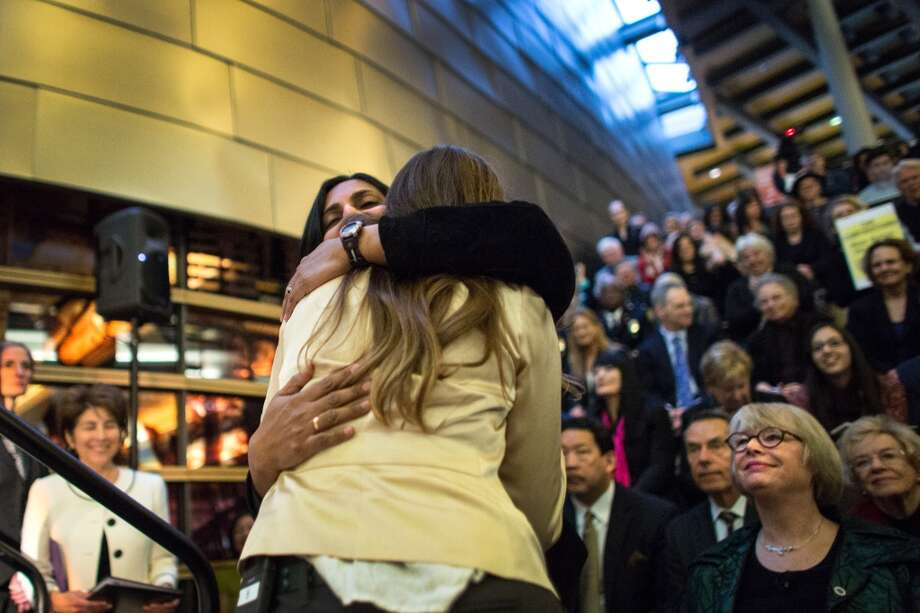 New Seattle City Councilmember Kshama Sawant is hugged by Nicole Grant on Monday, January 6, 2014 at Seattle City Hall before Sawant is sworn-in. Photo: JOSHUA TRUJILLO, SEATTLEPI.COM
