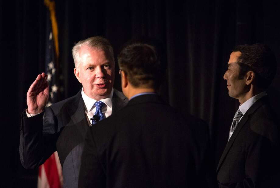 Seattle Mayor Ed Murray is sworn-in by former Governor and Ambassador to China Gary Locke on Monday, January 6, 2014 at Seattle City Hall. Hundreds of people packed the lobby of City Hall for the swearing in of city council members, the city attorney and the new mayor. Photo: JOSHUA TRUJILLO, SEATTLEPI.COM