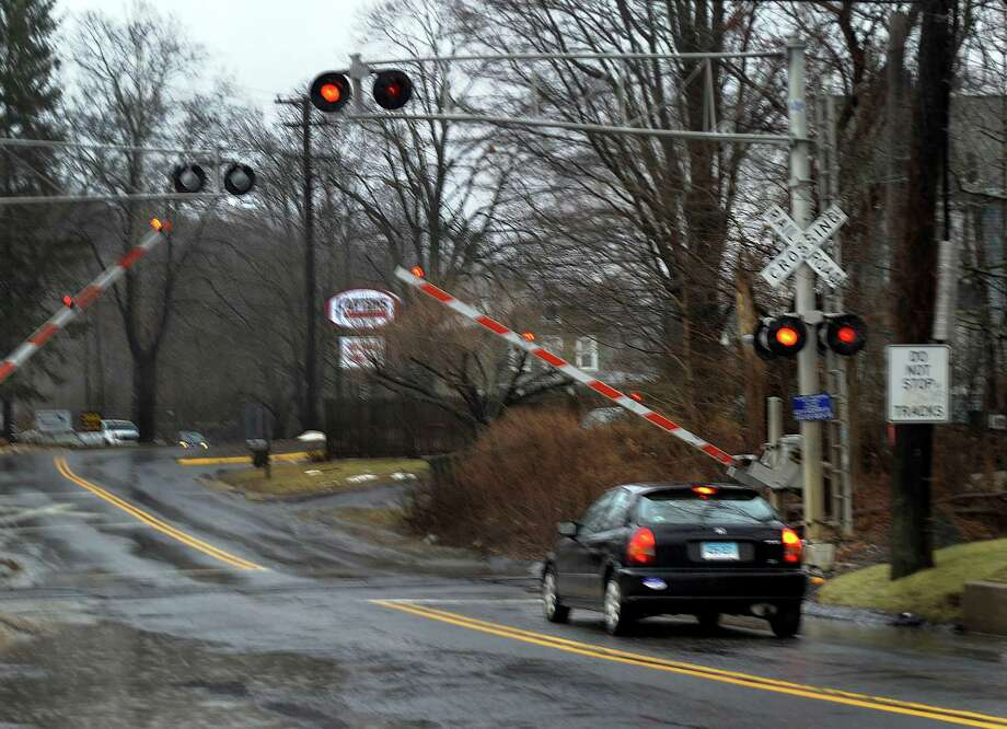 The arms of the crossing gates come down before the arrival of a Metro-North train at Shelter Rock Road in Danbury on Monday. Photo: Carol Kaliff / The News-Times