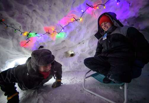 Eli Esch, 13, right, and his dad Tom enjoy the snow fort and igloo they built over the last few weeks, Monday Jan. 6, 2014 in Minneapolis. It is decked out with Christmas lights and the two spent the night in it last week. Eli was enjoying his day off school due to the cold but was relatively warm in the igloo.  Photo: Glen Stubbe, AP / The Star Tribune