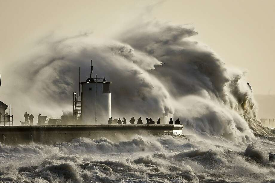Enormous waves break on Porthcawl harbor, South Wales, as strong winds, rain and high tides lash the country. At 
