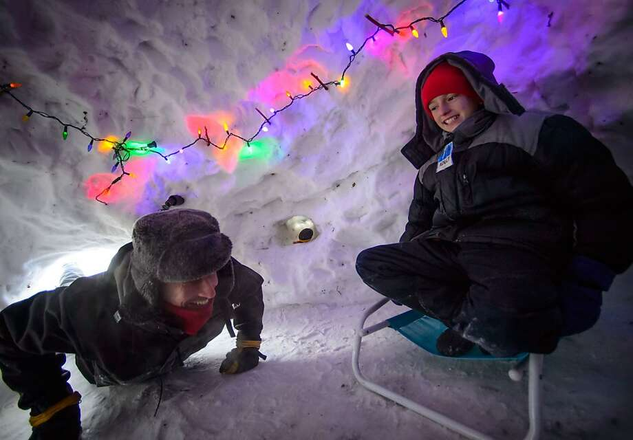 Eli Esch, 13, right, and his dad Tom enjoy the snow fort and igloo they built over the last few weeks, Monday Jan. 6, 2014 in Minneapolis. It is decked out with Christmas lights and the two spent the night in it last week. Eli was enjoying his day off school due to the cold but was relatively warm in the igloo. (AP Photo/The Star Tribune, Glen Stubbe) MANDATORY CREDIT; ST. PAUL PIONEER PRESS OUT; MAGS OUT; TWIN CITIES TV OUT Photo: Glen Stubbe, Associated Press