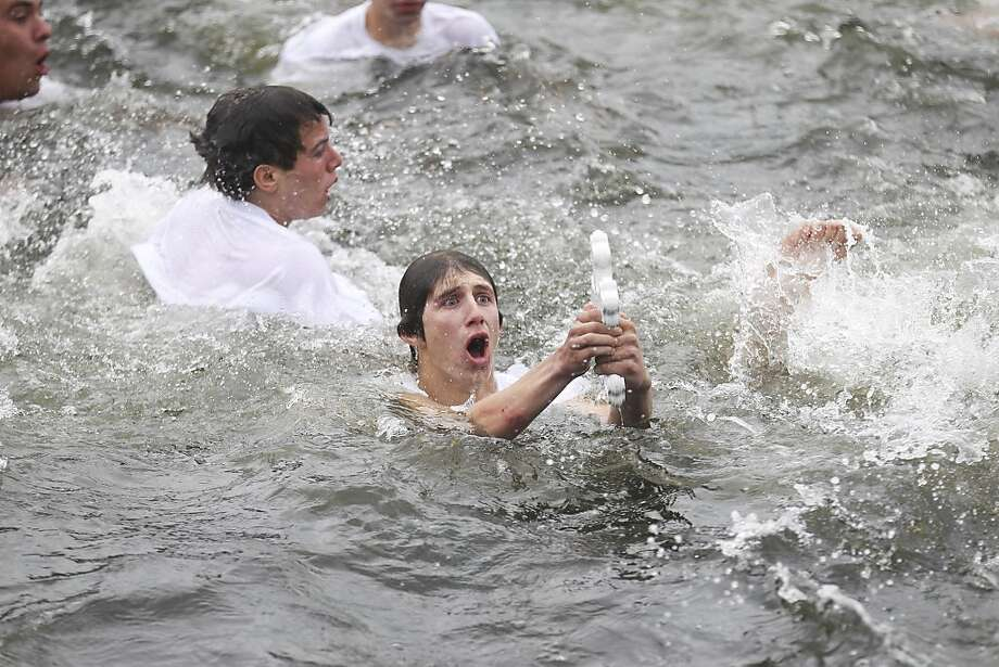 Peter Smith, 18 of Ellenton, Fla., emerges from the water after retrieving the cross during the 108th Epiphany celebration in Tarpon Springs, Fla., on Monday, Jan. 6, 2014. (AP Photo/Tampa Bay Times, Eve Edelheit) Photo: Eve Edelheit, Associated Press