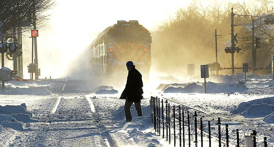 An outbound Metra commuter train gets lost in the blowing snow as man walks to the Arlington Heights, Ill.  train station in the sub-freezing temperatures on Monday, Jan. 6, 2014.  (AP Photo / Daily Herald,  Mark Welsh) Photo: Mark Welsh, Associated Press