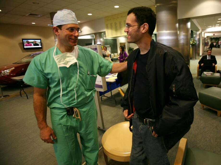 Chief of cardiothoracic surgery Rafael Squitieri, MD, left, greets Carlos Labrador, 37 of Bridgeport, at St. Vincent's Hospital in Bridgeport on Thursday, January 21, 2010. Squitieri performed a life saving operation on Labrador who suffered a pulmonary embolism on November 29, 2009. Photo: Brian A. Pounds / Connecticut Post