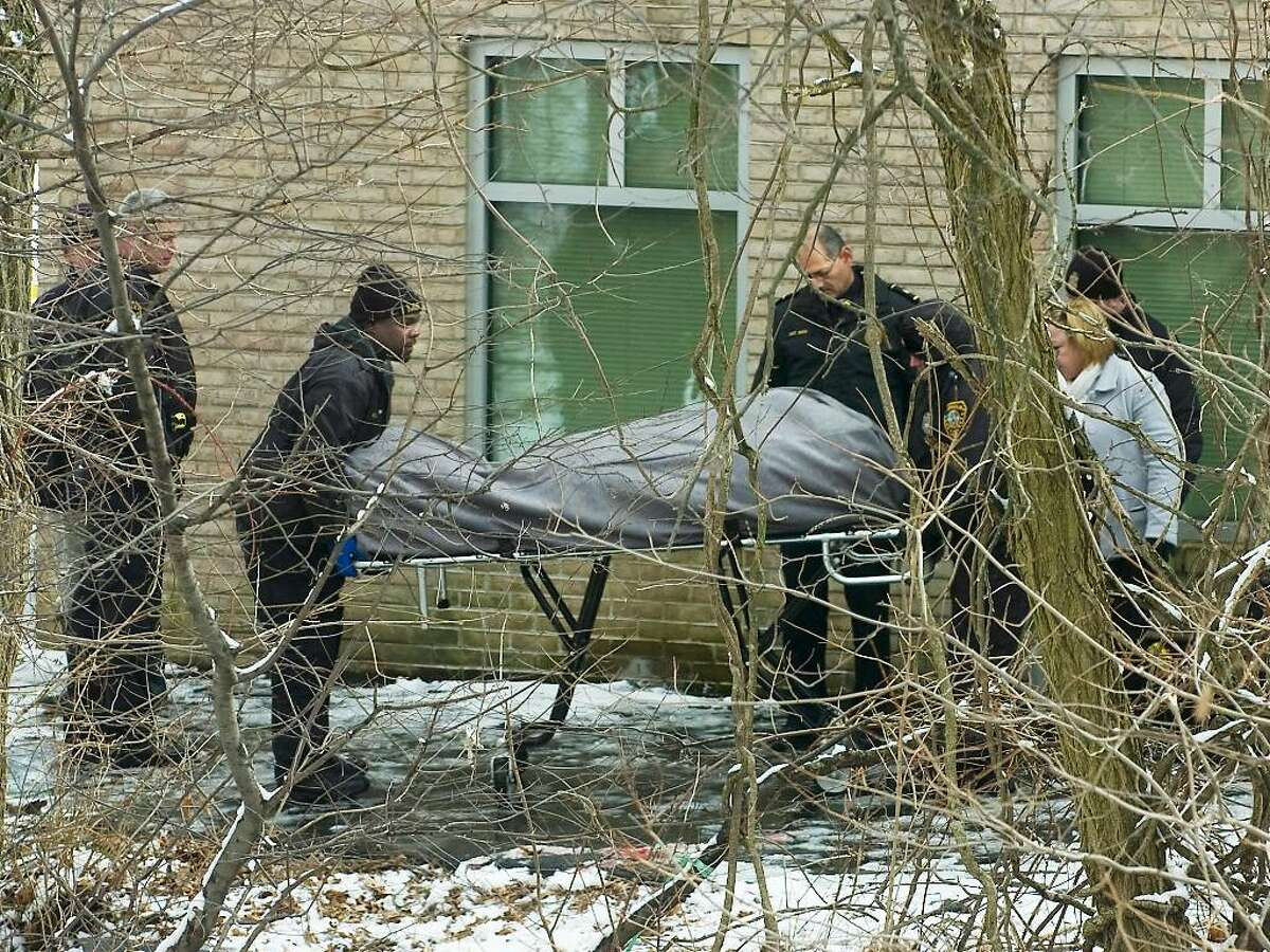 Norwalk police officers and detectives assist personnel from the state medical examiner's officer as they remove the body of Karl Savage, 30, of 93 Ferris Ave, Norwalk. His body was found this morning behind Nathaniel Ely Childcare Center in Norwalk, Conn. on Wednesday, Feb. 3, 2010.