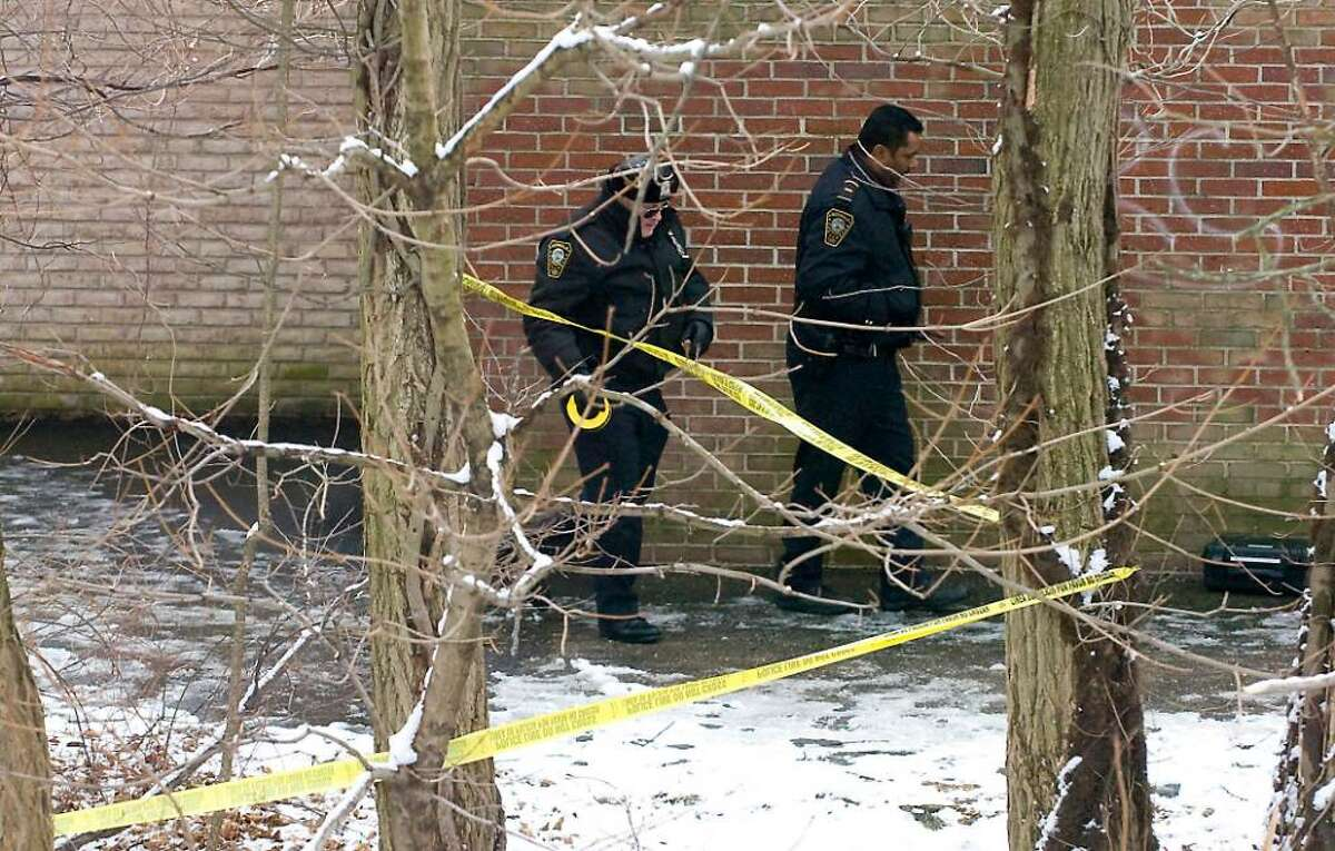 Norwalk police officers and detectives investigate the scene where the of Karl Savage, 30, of 93 Ferris Ave, Norwalk, was found behind Nathaniel Ely Childcare Center in Norwalk, Conn. on Wednesday, Feb. 3, 2010.