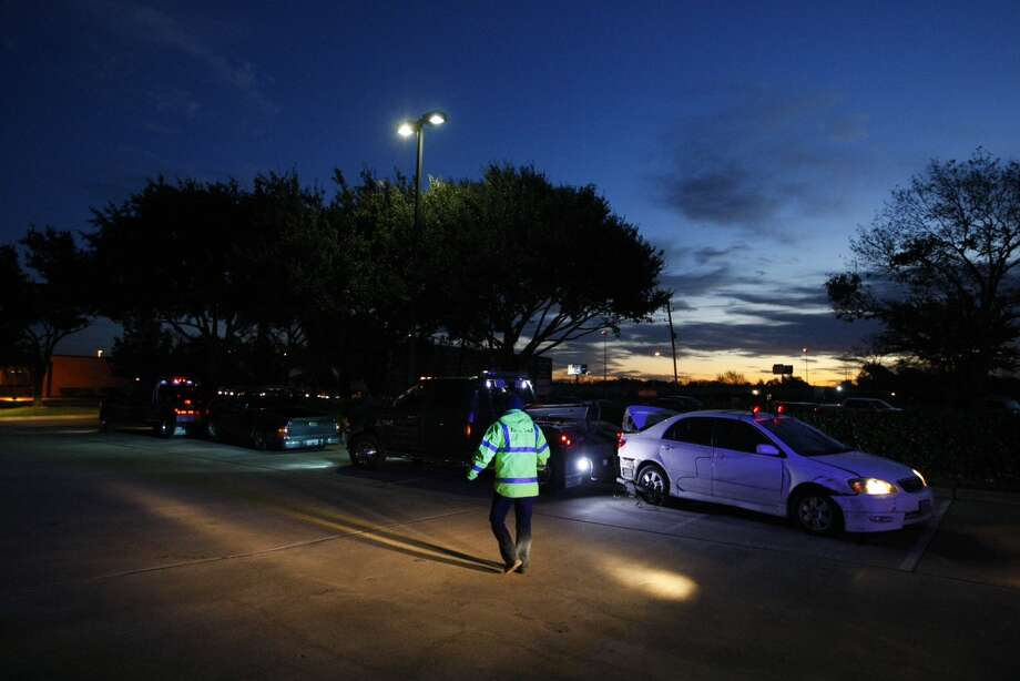 Two vehicles involved in an ice-related accident wait to be towed before dawn Tuesday on Gessner near Hempstead. Photo: Cody Duty, Houston Chronicle