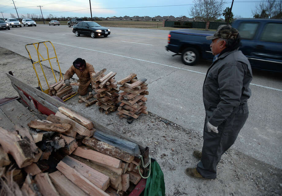 Alex Contreras, left and Allen Contreras sell split wood to commuters on Major Drive Monday evening. Alex Contreras said business has been busy due to the recent freezing temperatures. Photo taken Monday, January 06, 2014 Guiseppe Barranco/@spotnewsshooter Photo: Guiseppe Barranco, Photo Editor