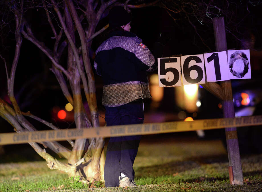 Police search the area around a body on Lancaster Lane on Monday night. There was a fatal shooting Monday night in front of 5630 Lancaster Lane. Sergeant Barton told media that there was one deceased individual and that one person was in custody. According to the sergeant, witnesses say that it was a domestic dispute. Photo taken Monday, 1/6/14 Jake Daniels/@JakeD_in_SETX Photo: Jake Daniels / ©2013 The Beaumont Enterprise/Jake Daniels