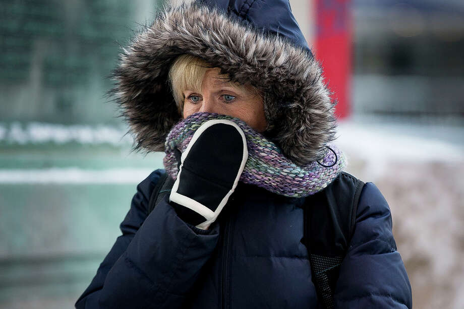 A woman shields her face as she departs from Union Station with wind chills nearing minus 30 Fahrenheit on Tuesday, Jan. 7, 2014, in downtown Chicago.  Dangerously cold polar air snapped decades-old records as it spread Tuesday from the Midwest to southern and eastern parts of the U.S. and eastern Canada, making it hazardous to venture outside and keeping many schools and businesses closed. Photo: Andrew Nelles, ASSOCIATED PRESS / AP2014