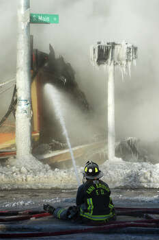 An Ann Arbor firefighter sprays down a section of the building as icicles form on posts while fire engulfs Happy's Pizza in Ann Arbor, Mich., on Tuesday, Jan. 7, 2014.   Firefighters worked for several hours in temperatures that dipped to 15 degrees below zero to extinguish a blaze at the pizza shop. No injuries were reported following the fire. Photo: Melanie Maxwell, AP / The Ann Arbor News