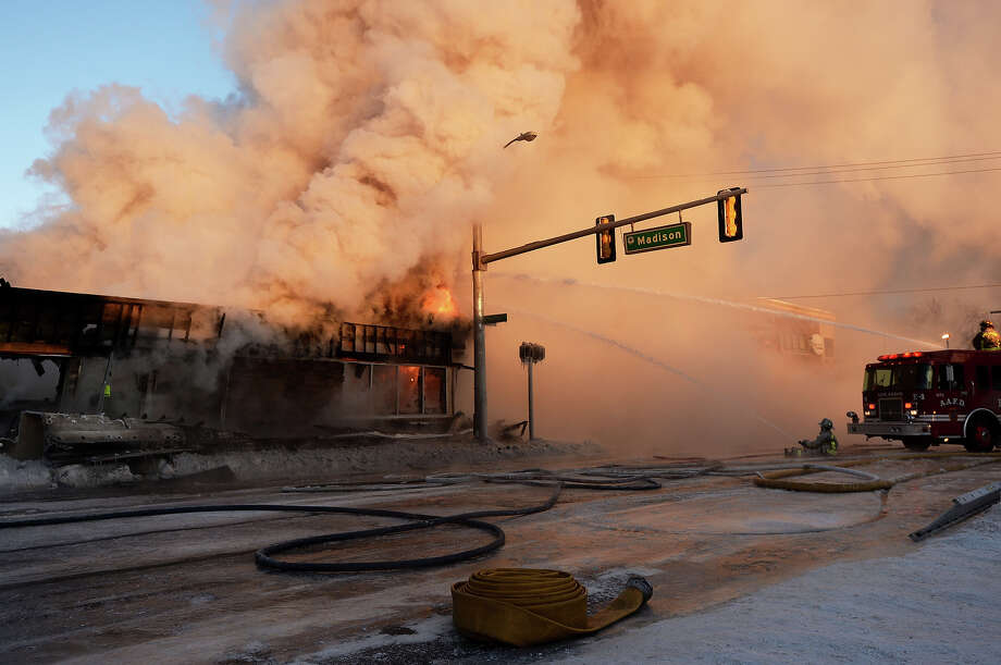 Ann Arbor firefighters work to put out a fire that engulfed Happy's Pizza in Ann Arbor, Mich., on Tuesday, Jan. 7, 2014.   Firefighters worked for several hours in temperatures that dipped to 15 degrees below zero to extinguish a blaze at the pizza shop. No injuries were reported following the fire. Photo: Melanie Maxwell, AP / The Ann Arbor News