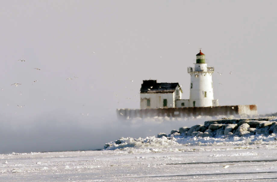 Ice fog partially shrouds the lighthouse at the entrance to Cleveland harbor Tuesday, Jan. 7, 2014.   An official low of -11 degrees in Cleveland broke the old record of -9 set in 1884. Photo: Mark Duncan, AP / AP