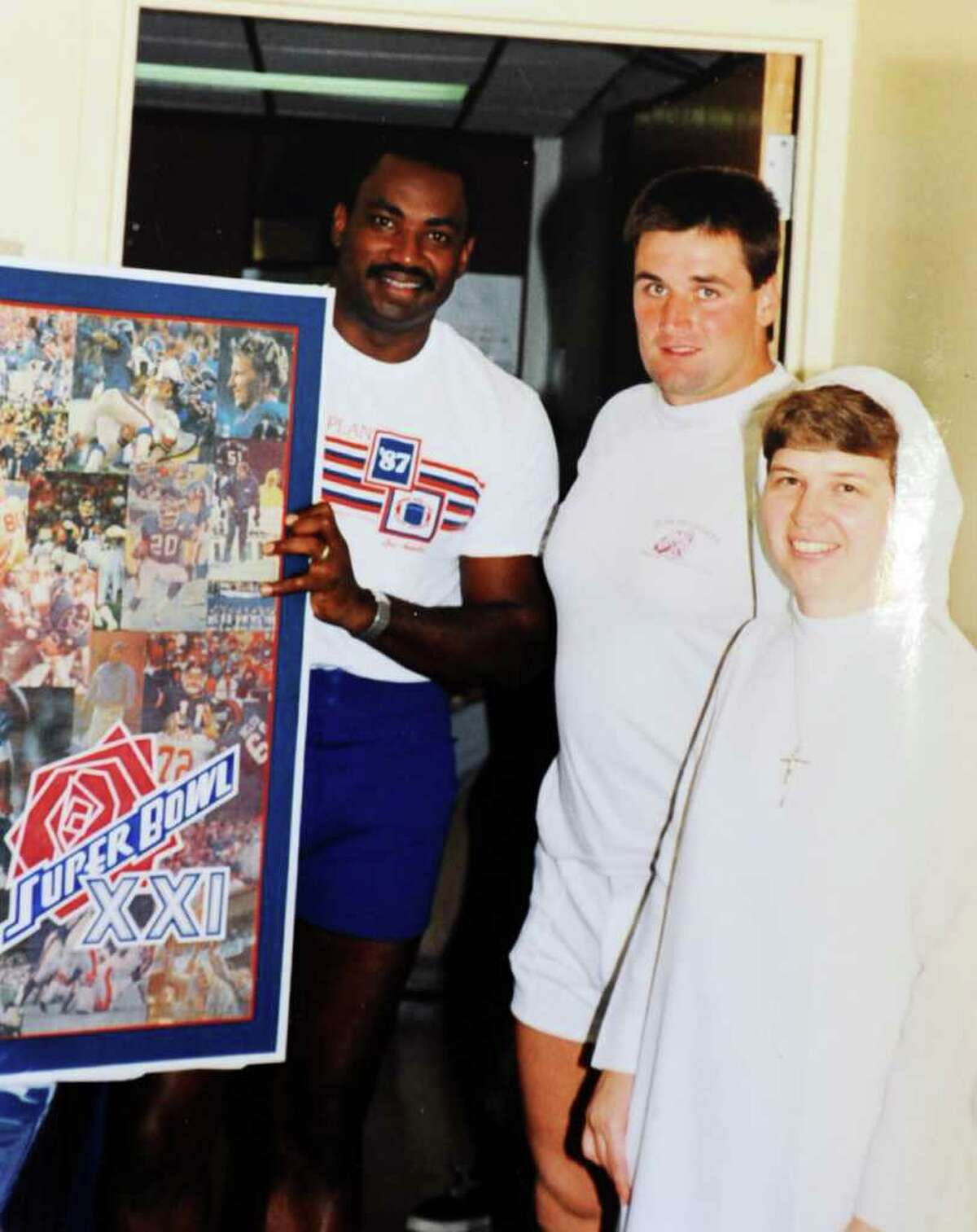 Sister Carol Ann with former New York Giants players George Martin and Jim Burt with a collage she made for the team.