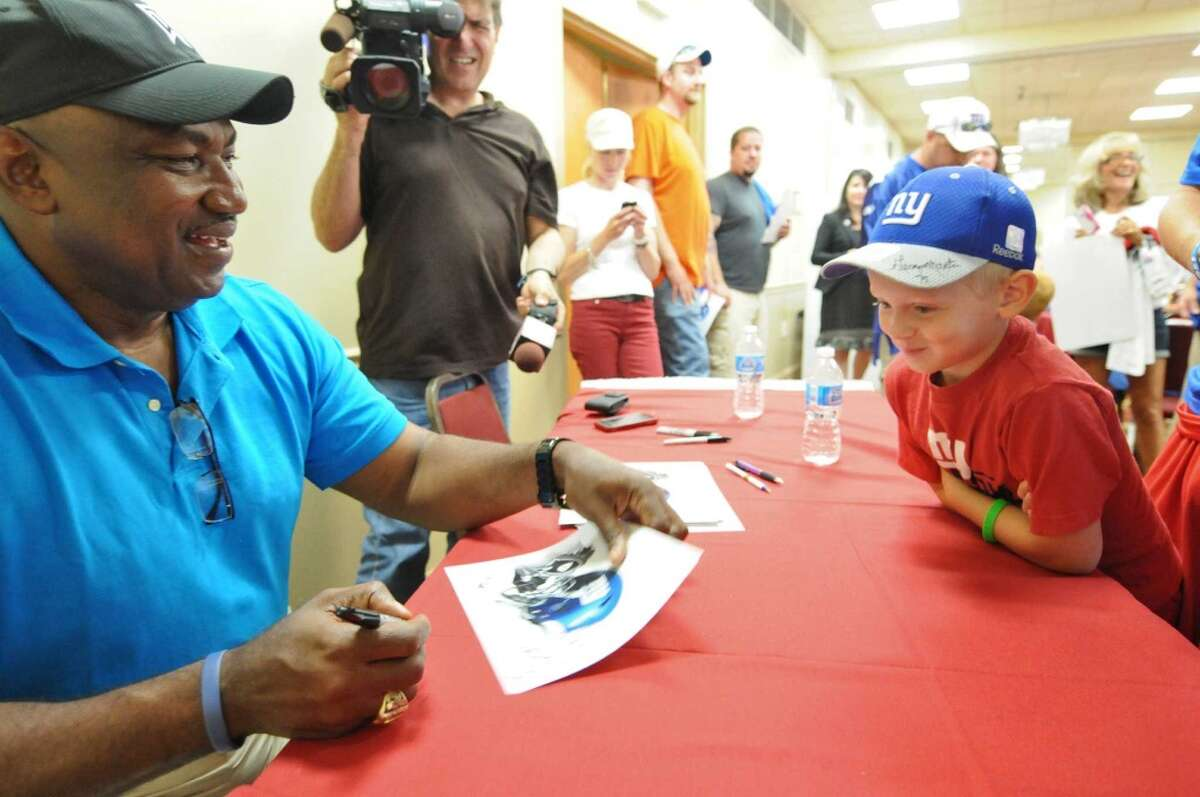 New York Giants great George Martin signs an autograph for life long Giants fan Ayden Swears of Fort Edward, 8, after his father Phil gave blood during the American Red Cross New York Giants Training Camp Blood Drive at the Best Western, on Thursday Aug. 2, 2012 in Albany, NY. (Philip Kamrass / Times Union)