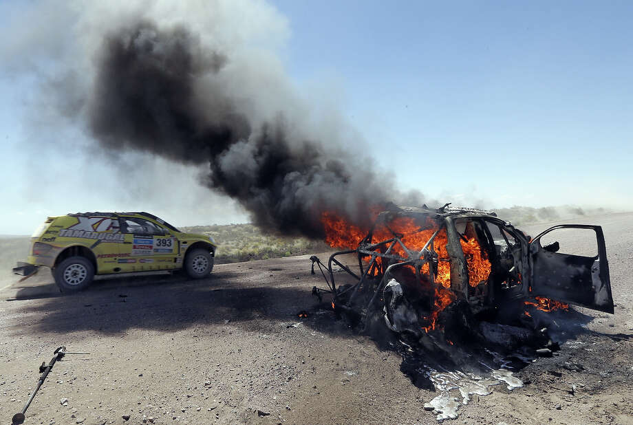 Chile's Javier Campillay drives past the burning car of Kazakhstan's Bauyrzhan Issabayev and Gabdulla Ashimov during the Dakar Rally 2014 Stage 2 from San Luis to San Rafael, on January 6, 2014. Photo: AFP, AFP/Getty Images / 2014 AFP