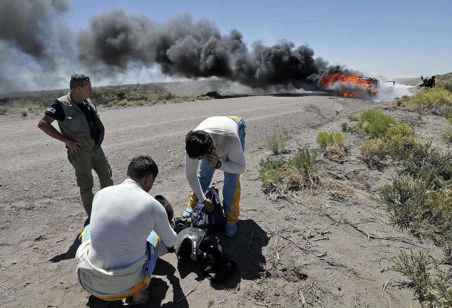 Kazakhstan's pilots Bauyrzhan Issabayev and Gabdulla Ashimov stand next to their burning car, during the Dakar Rally 2014 Stage 2 from San Luis to San Rafael, on January 6, 2014. Photo: AFP, AFP/Getty Images / 2014 AFP