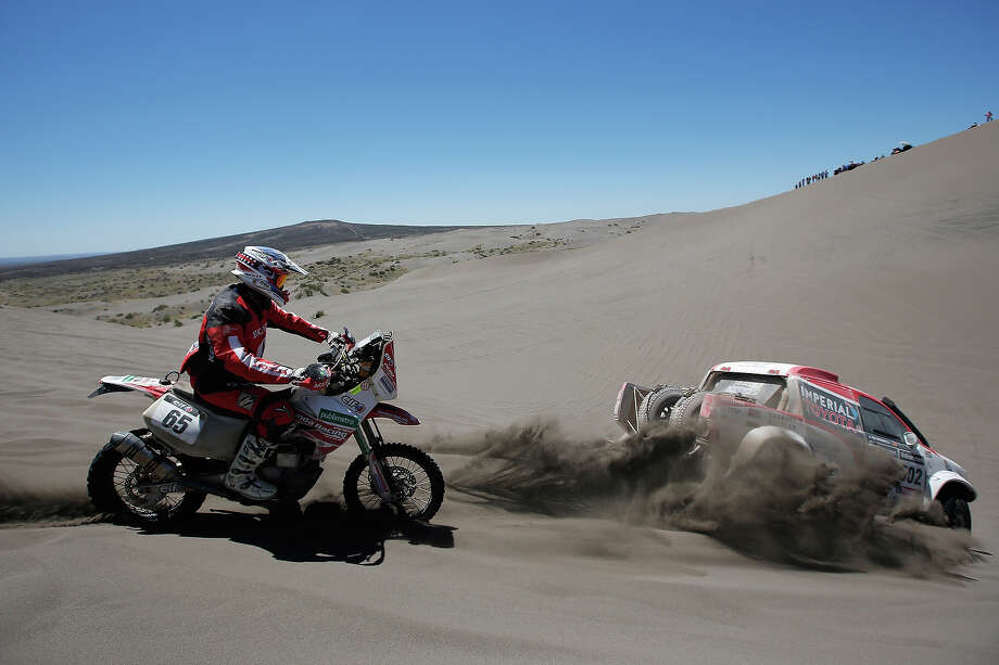 Eduardo Heinrich of Peru for Honda Racing Peru and (#302) Giniel De Villiers of South Africa and Dirk Von Zitzewitz of Germany for Imperial Toyota compete on Day 2 of the Dakar Rally 2014 on January 6, 2014 in the Dunes of Nihuil, Argentina. Photo: Dean Mouhtaropoulos, Getty Images / 2014 Getty Images