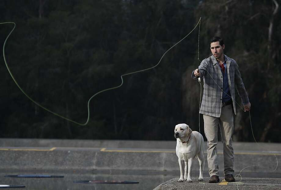 George Revel and his dog Diesel at the ponds of the Golden Gate Casting and Angling Club in S.F Photo: Liz Hafalia, The Chronicle