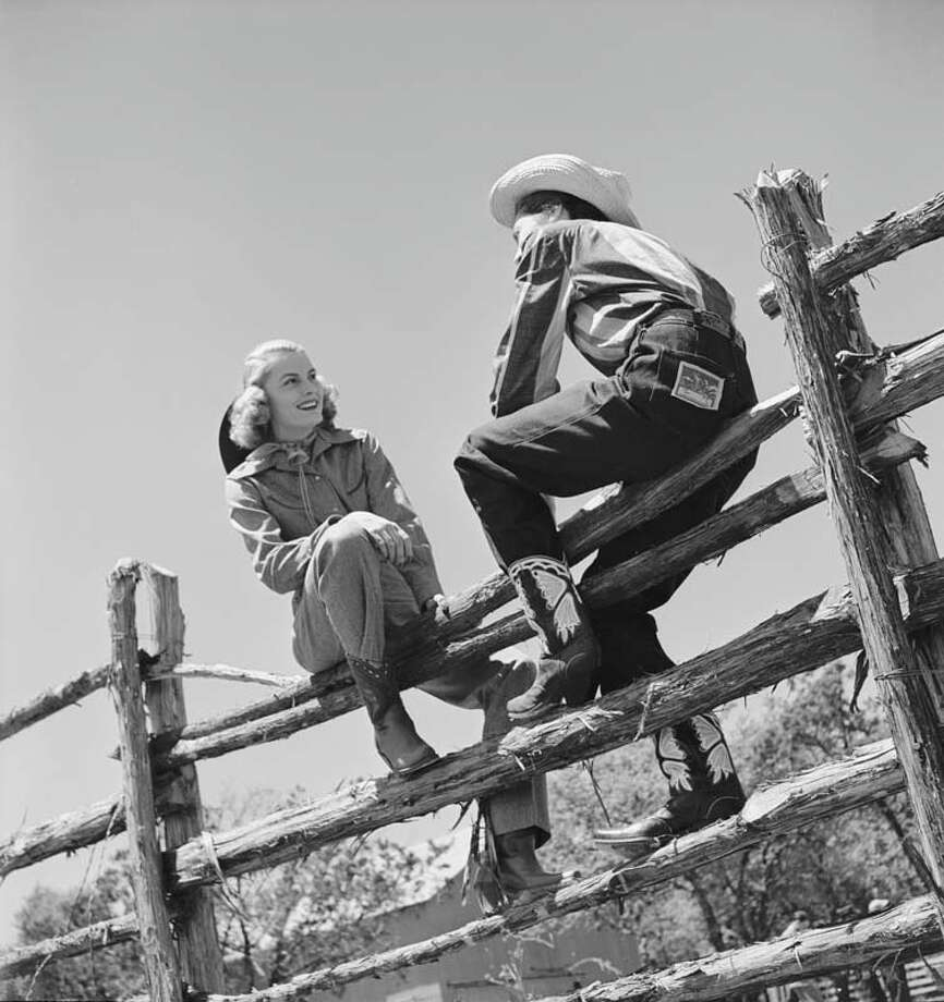 A pair of unidentified guests at the Flying L Ranch sit on a split-rail fence, Bandera, Texas, May 1947. The ranch, built by wealthy Texas Oilman Colonel Jack Lapham, was conceived as a combination airport, resort, and dude ranch. Take a look back at Texas ranches from throughout the 1900s. (Photo by Cornell Capa/Time & Life Pictures/Getty Images) Photo: Cornell Capa, Time & Life Pictures / Time & Life Pictures