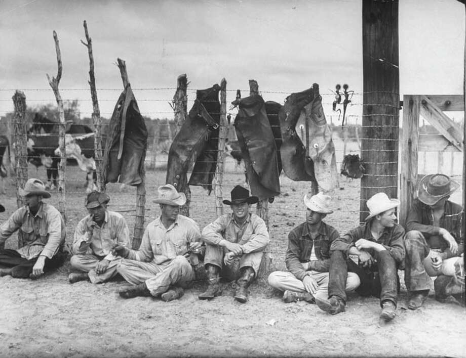 Seven cowboys sit along corral fence draped with their chaps, which they don't wear while not at work, as they wait for brand irons to heat up during cattle roundup at Matador Ranch, the second largest in the state.  (Photo by Hansel Mieth//Time Life Pictures/Getty Images) Photo: Hansel Mieth, Time & Life Pictures/Getty Image / Time Life Pictures