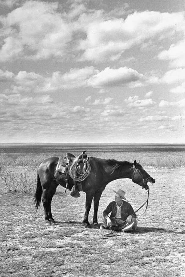 The foreman of the J.A. Ranch Clarence Hailey Long sits in shade of his horse on prairie.  (Photo by Leonard Mccombe//Time Life Pictures/Getty Images) Photo: Leonard McCombe, Time & Life Pictures/Getty Image / Leonard Mccombe