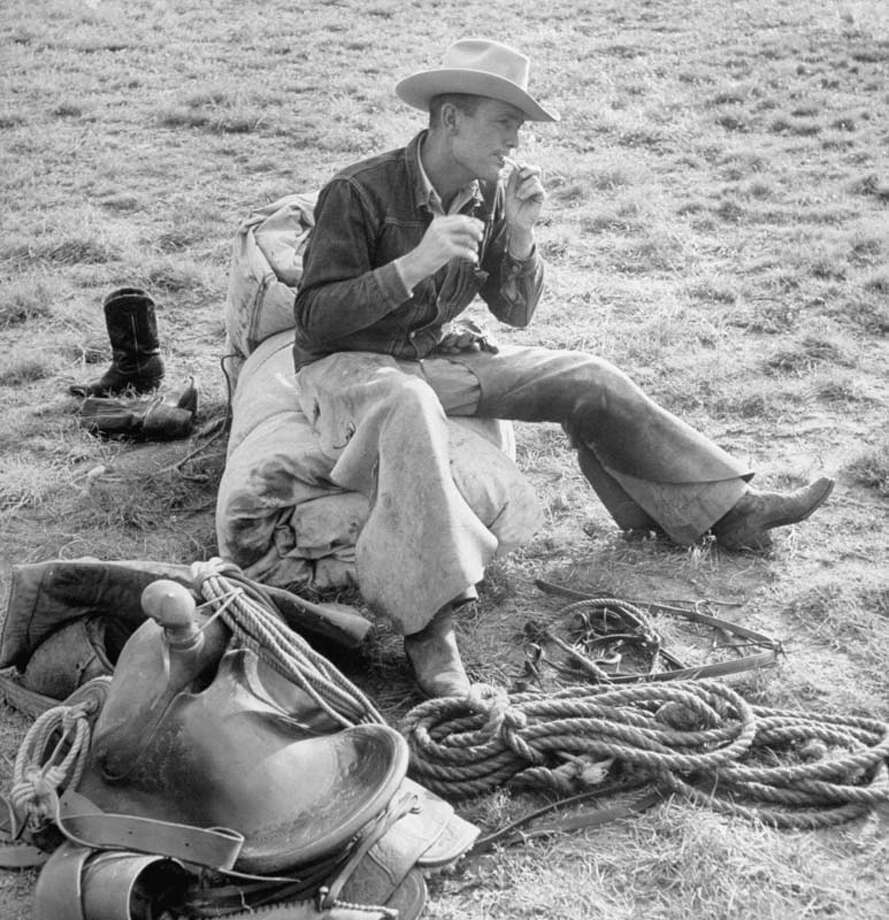 Cowboy Clarence H. Long is pictured sitting down and rolling cigarette.  (Photo by Leonard Mccombe//Time Life Pictures/Getty Images) Photo: Leonard McCombe, Time & Life Pictures/Getty Image / Leonard Mccombe