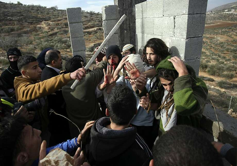 Below: Palestinians hit settlers while others try to stop them near West Bank village of Qusra. Photo: Nasser Ishtayeh, Associated Press