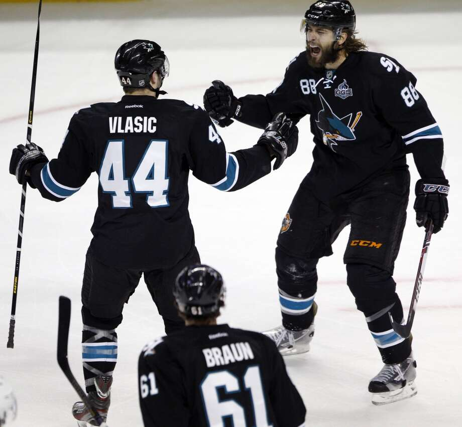 Brent Burns celebrates his goal with teammates, Marc-Edouard Vlasic and Justin Braun. Photo: Carlos Avila Gonzalez, The Chronicle