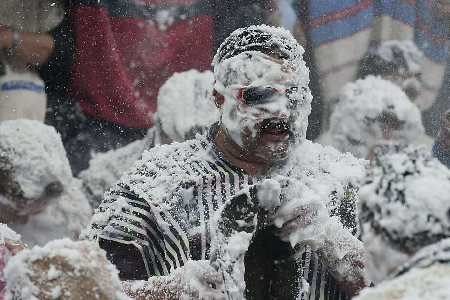 "Shaving-cream storm: The unseasonal ""snow"" covering revelers at the Carnival of Blacks and Whites in Pasto, Colombia, is actually foam and talc powder. Photo: Luis Robayo, AFP/Getty Images"