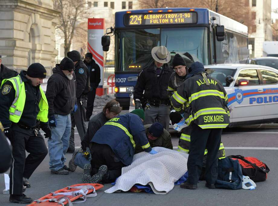 Fire and EMS personnel care for the victim of a bus accident near the Washington Avenue entrance to the State Capitol Tuesday afternoon, Jan. 7, 2014, in Albany, N.Y. (Skip Dickstein / Times Union) Photo: SKIP DICKSTEIN