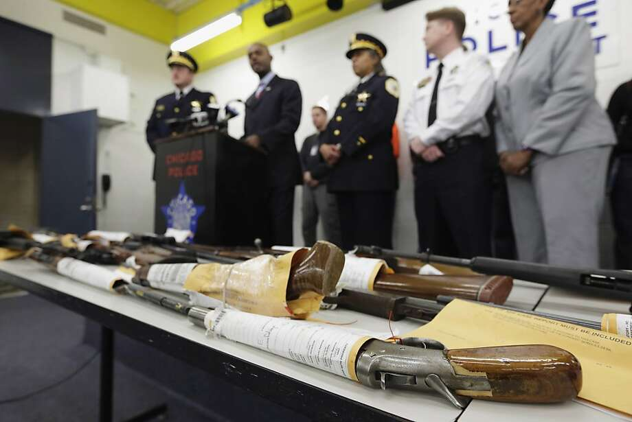 FILE - In this Jan. 28, 2013, file photo, Chicago Police First Deputy Superintendent Alfonsa Wysinger, second from left, speaks at a news conference in Chicago with a display of recently seized guns, part of the 574 that had been seized in the city since Jan. 1. The mounting homicide toll in President Barack Obama's hometown has giving ammunition to both sides in the nation's debate about gun rights and safety. On Monday, Jan. 6, 2014, a federal judge in Chicago potentially opened a new market to gun dealers after ruling as unconstitutional Chicago ordinances that aim to reduce gun violence by banning their sale within the city's limits. (AP Photo/M. Spencer Green, File) Photo: M. Spencer Green, Associated Press