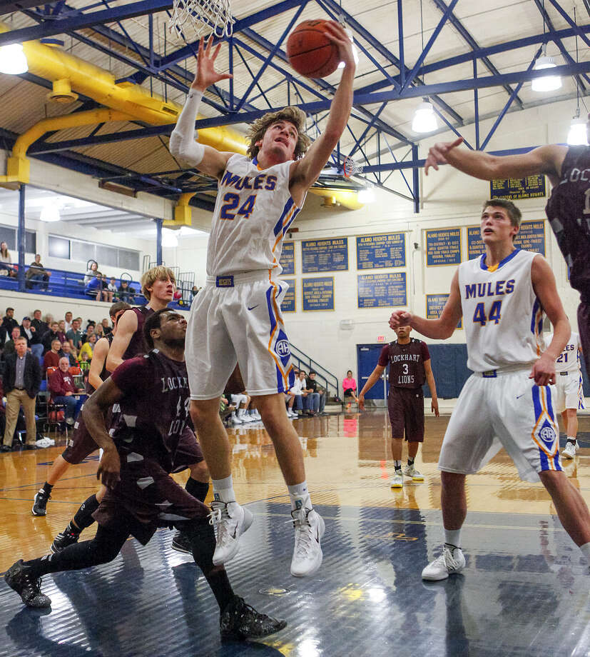 Alamo Height's Max Riemenschneider, (24), pulls down an offensive rebound as Ben Lammers, (44), looks on during the second quarter of their game with Lockhart  Friday at the Alamo Heights gym. The Mules beat the Lions, 79-44. Photo: Marvin Pfeiffer / North Central News / Prime Time Newspapers 2013